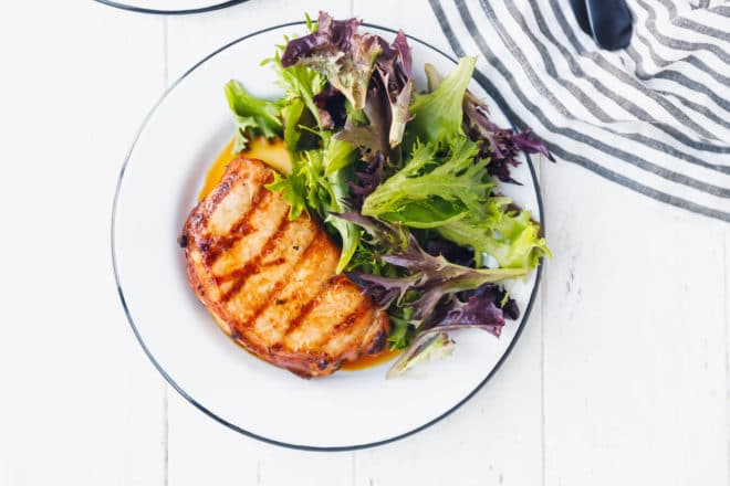 Grilled pork chops on a white plate with salad