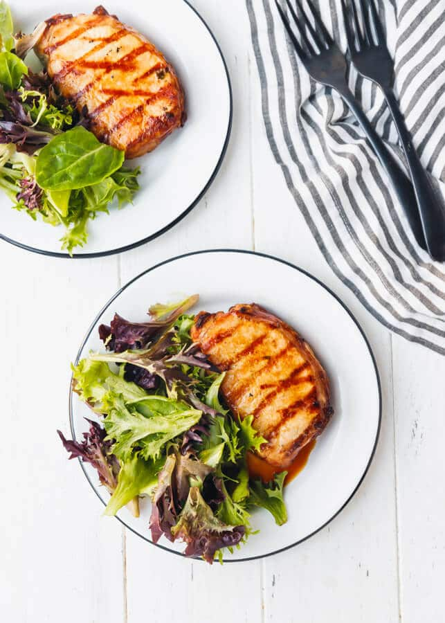 Grilled pork chops with mixed greens on plates