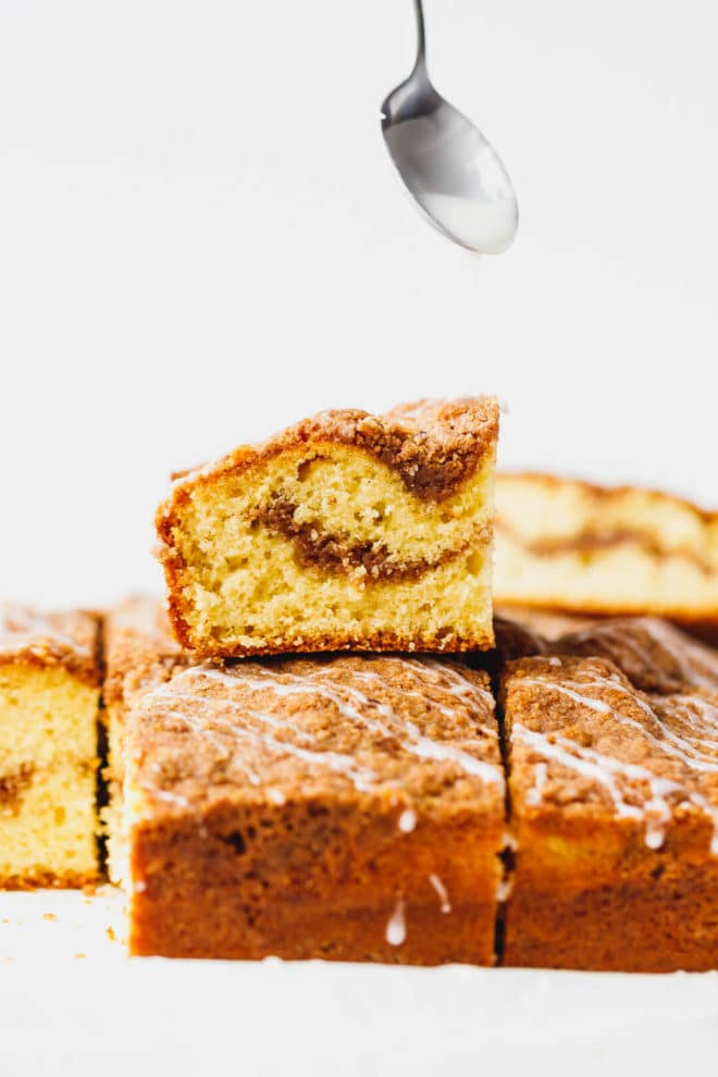 Cinnamon coffee cake cut into squares drizzled with glaze