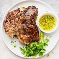 Grilled t bone steak on a white plate