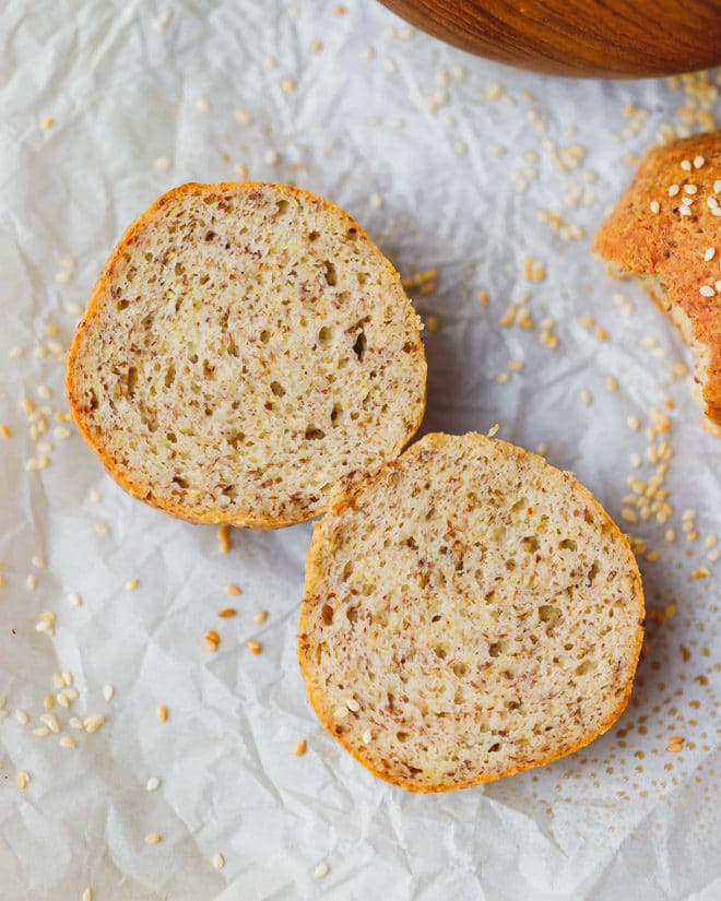 Keto bread roll cut in half on parchment paper