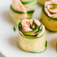 Smoked salmon and cucumber appetizer rolls on a white plate