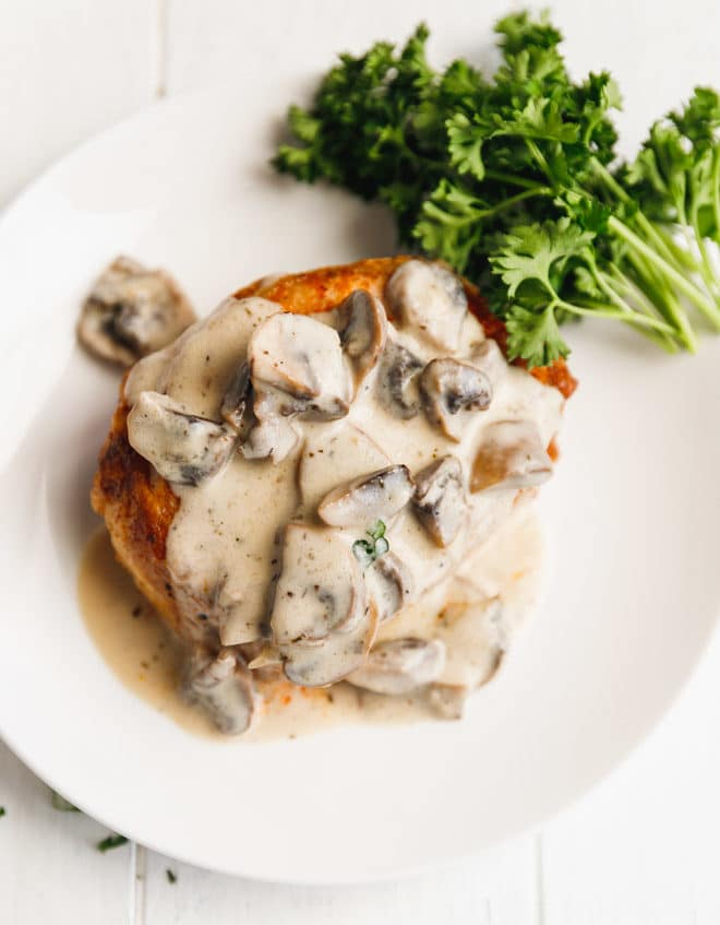 Creamy mushroom sauce over a pork chop on a plate