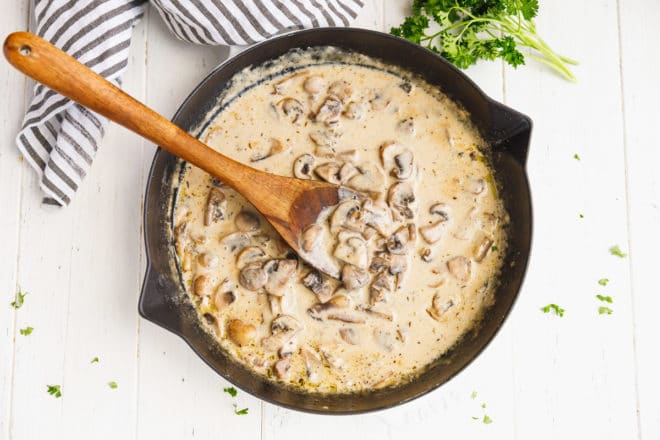 A pan filled with creamy mushroom sauce and a wooden spoon