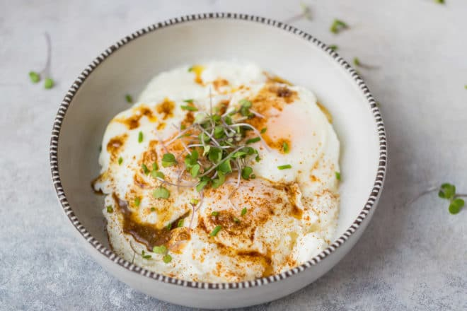 Cilbir eggs turkish eggs in yogurt in a ceramic bowl