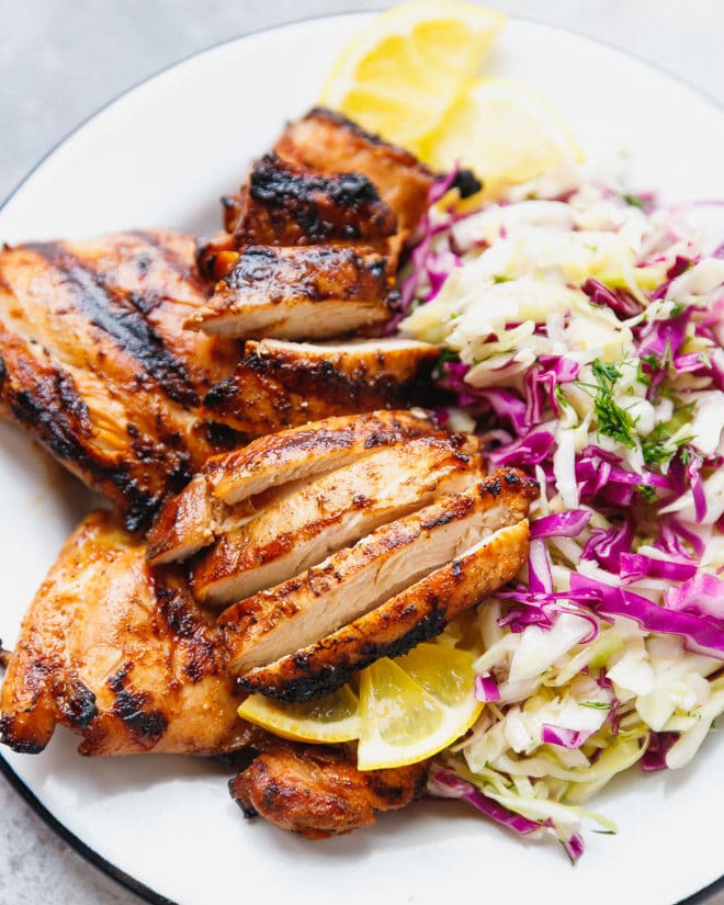 Grilled chicken thighs cut and placed on a plate with cabbage salad