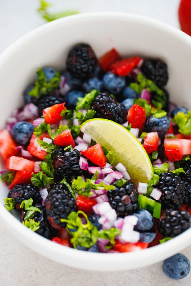 Berry salsa in a bowl topped with lime
