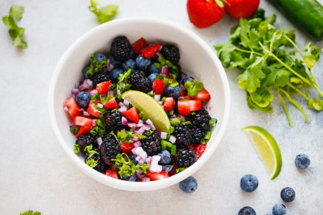 Salsa with berries in a small white ceramic bowl