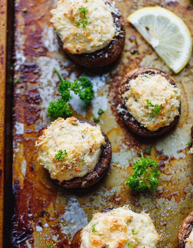 Crab stuffed mushrooms on a cookie sheet