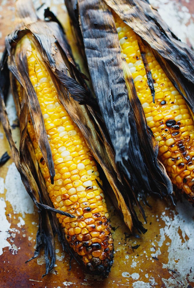 Ears of corn on te cob grilled with the husk on
