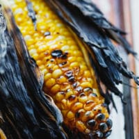 Grilled corn on the cob in husk on a baking dish