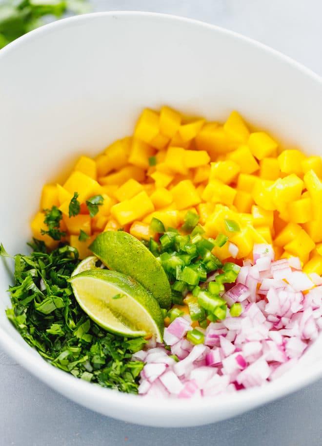 Chopped mango, cilantro, onion and jalapeños in a white bowl