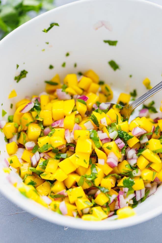 Colorful mango salsa in a white ceramic bowl