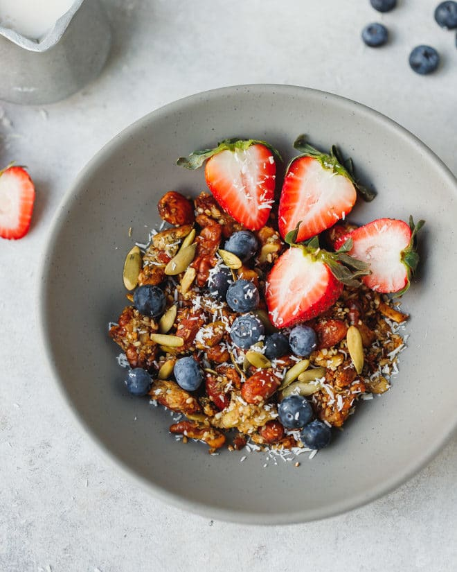 Keto granola with strawberries in a gray cereal bowl