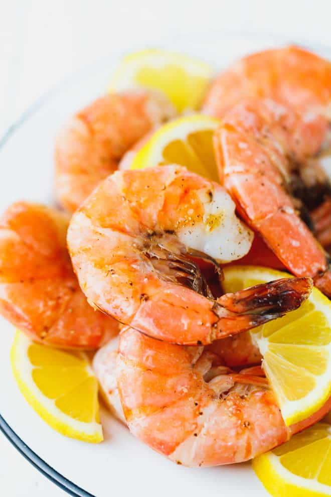 Broiled unpeeled shrimp on a white plate
