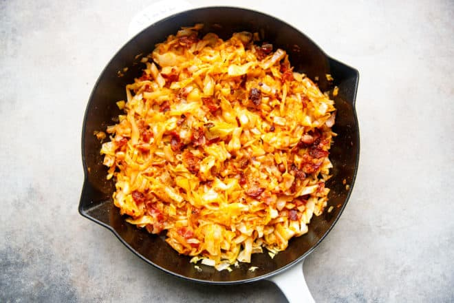 Bacon and cabbage in a white skillet