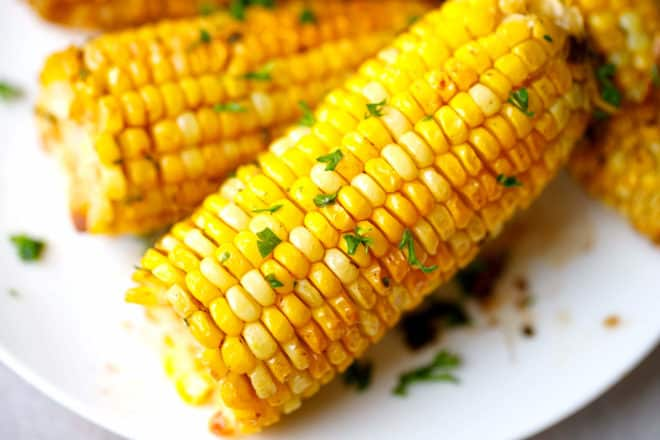 Ears of baked corn on the cob on a plate