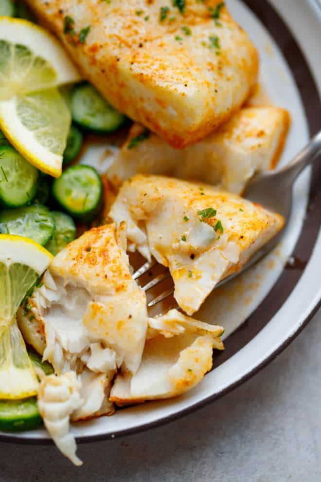 Baked Halibut on a plate with cucumbers