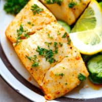 Baked halibut fillet on a white plate