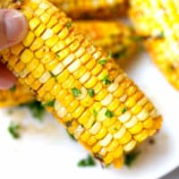 A hand holding corn on the cob