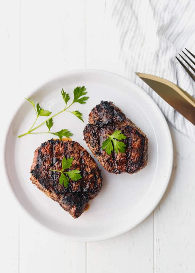 two grilled filets mignon on a white plate