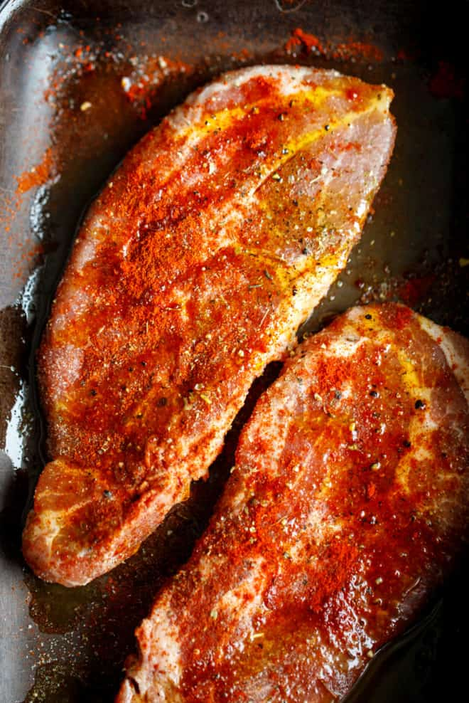 Seasoned pork chops in a pan