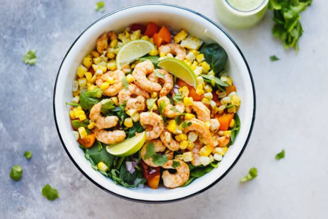 A white bowl full with Tequila lime shrimp salad with cilantro lime dressing