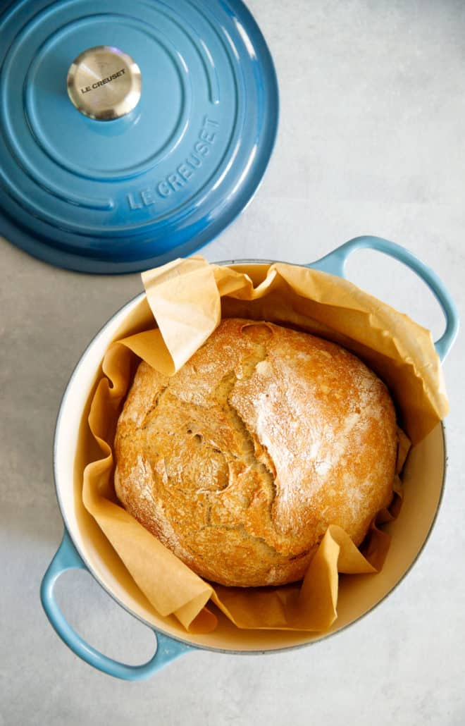 Baked bread inside a blue Le Creuset Dutch oven