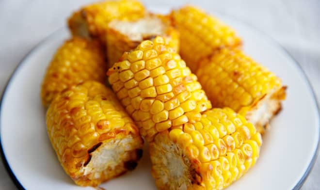 Corn cut into quarters and air fried placed on a plate