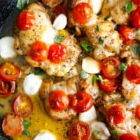 A pan qith chicken thighs fresh mozzarella and cherry tomatoes