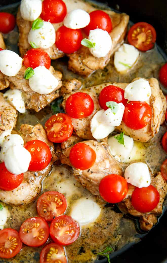 Boneless skinless chicken thighs in a pan with cherry tomatoes and baby mozzarella