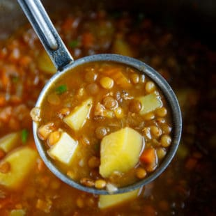 A ladle filled with Easy lentil soup with potatoes