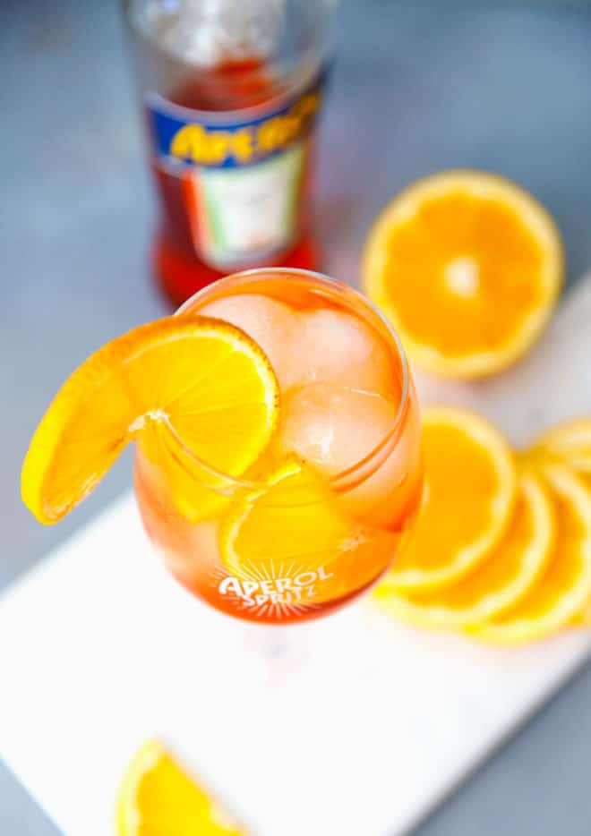 A glazz filled with ice and Aperol Spritz with orange round