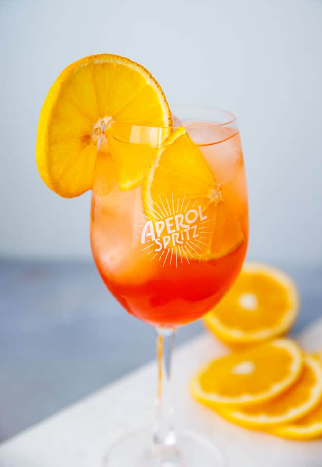 Aperol spritz in a clear wine glass with an orange slice