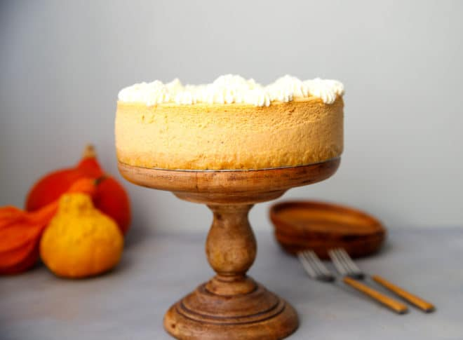 Keto pumpkin cheesecake on a wooden cake stand