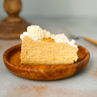 A slice of low carb pumpkin cheesecake with whipped cream on a wooden plate
