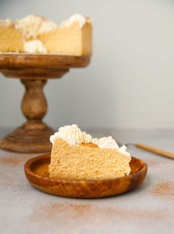 A slice of low carb pumpkin cheesecake on a wooden plate