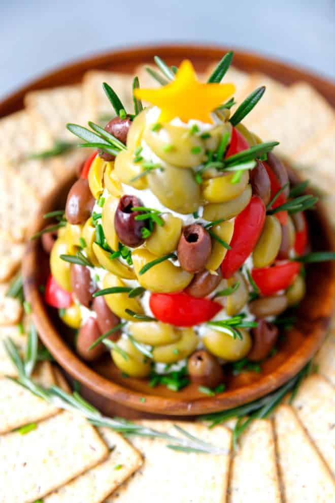 Christmas tree shaped cheese ball with olives, tomatoes and rosemary