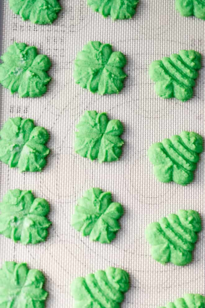 Clover and tree shaped Spritz cookies on a baking sheet