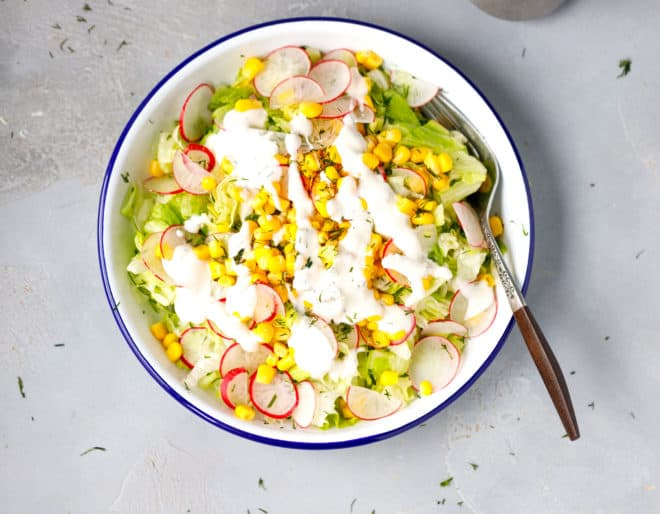 White bowl with iceberg lettuce salad and yogurt garlic dressing