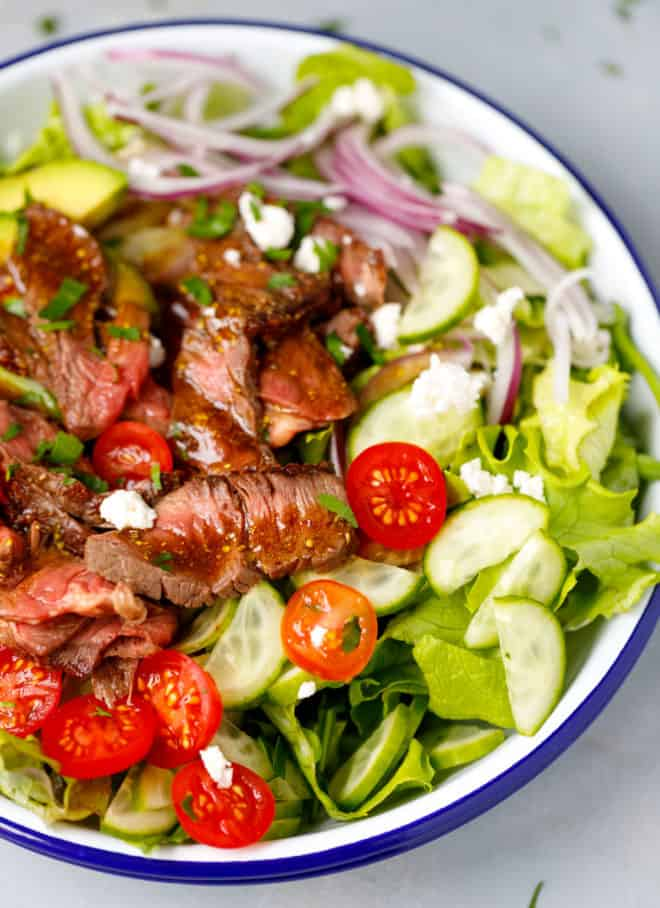 A bowl with mixed greens and steak