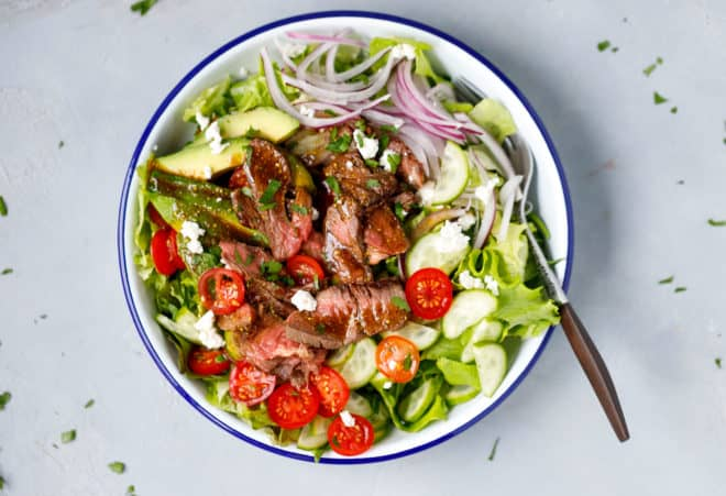 A bowl with steak salad and balsamic dressing