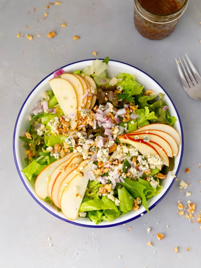 Apple walnut salad recipe in a salad bowl with dressing next to it