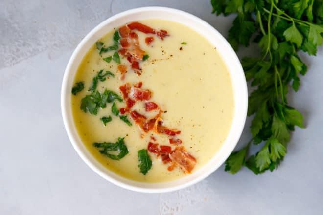 A bowl with potato leek soup and bacon