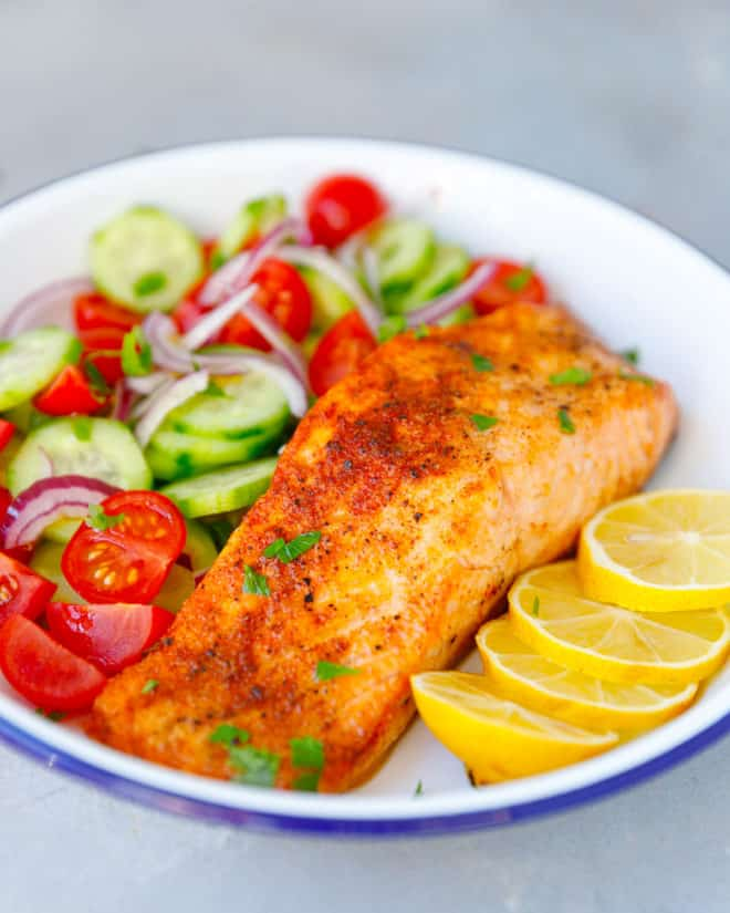 A white plate with air fryer salmon fillet and salad