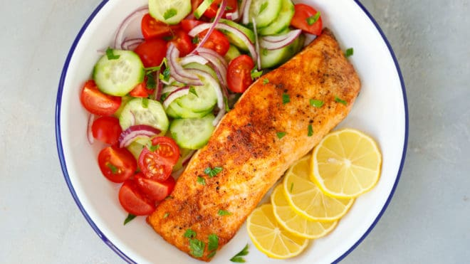 Air fryer salmon with tomato cucumber salad on a plate