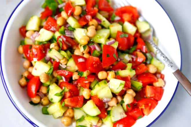 Tomato cucumber chickpea salad in a white metal bowl