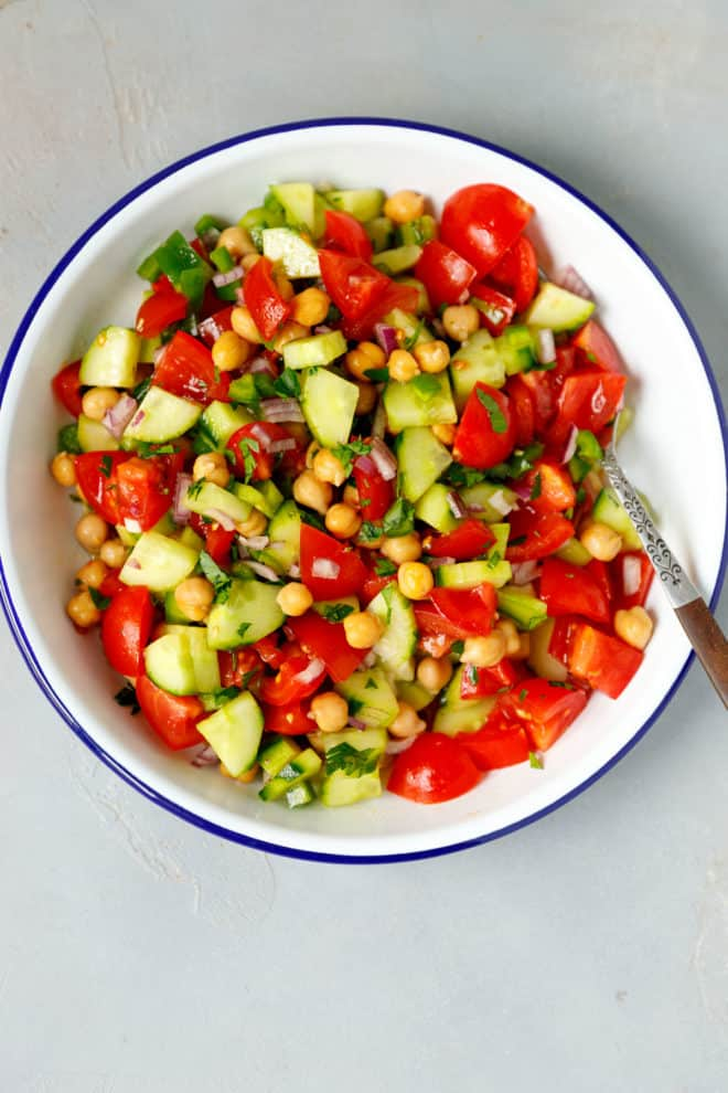 A bowl with cold chickpea salad and a fork