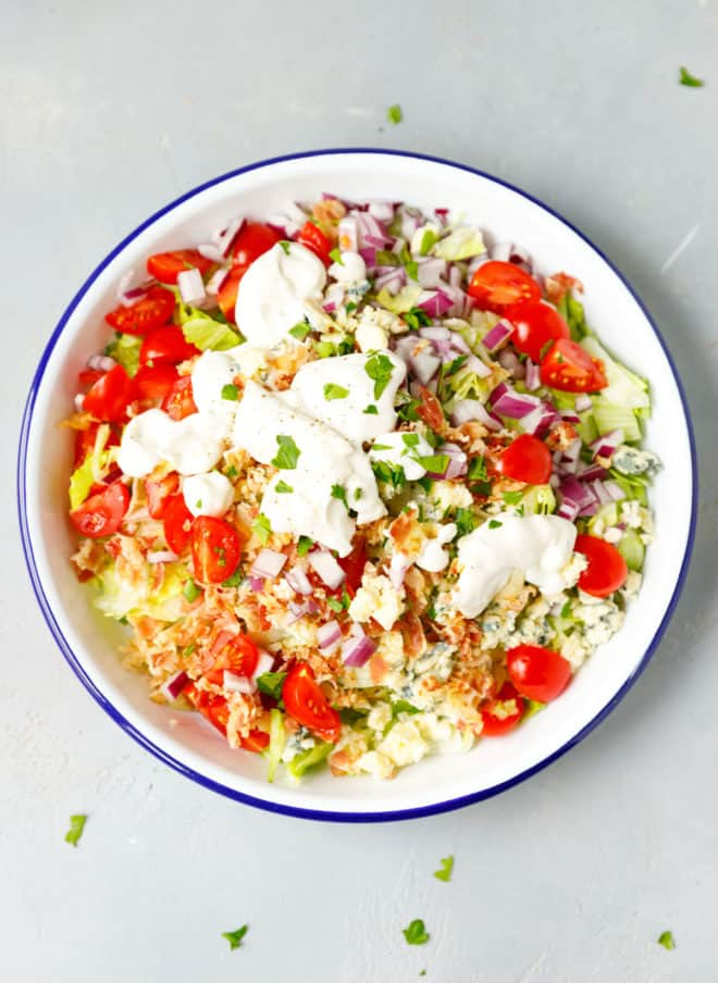 A chopped wedge salad in a white bowl, topped with blue cheese dressing
