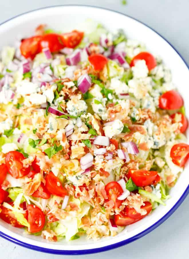 A white bowl with chopped iceberg wedge salad inside